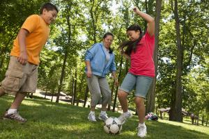 A woman plays soccer at a park with two teens