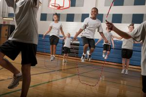 A group of children jump rope in a gymnasium