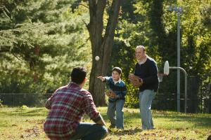 A boy plays baseball with his father and grandfather in a park