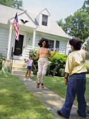 A mom and two children jumping rope in the front yard