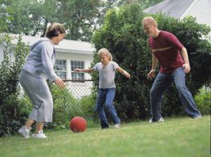 A mother and father kicking a ball in the backyard with their pre-teen daughter