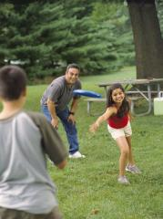 A girl plays frisbee with her family