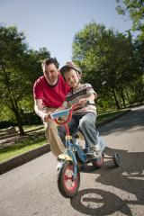 A man helping a young boy learn to ride a bike with training wheels.