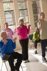A group of older adults lifting handweights in an exercise class