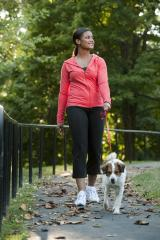 A woman walking her dog on an paved walking path