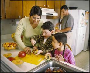 A mother and two children prepare fruit salad by the sink while father pours juice from a pitcher in the background
