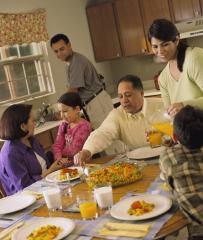 A Latino family of six (mother, father, two young children and grandparents) sitting around a table kitchen table for dinner.