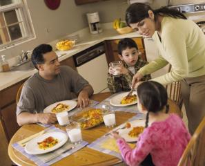 A Latino family of four sitting around a table kitchen table for dinner.
