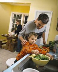 A father and son preparing a salad by the kitchen sink while the mother sets the table in the background