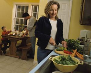 A mother preparing vegetables near the sink while father and son set the table in the background.