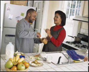 A man and pregnant woman snack on apples with peanut butter