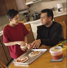 A father and son make pizzas