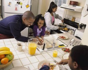 A man and his daughter wash their hands while a woman prepares breakfast in the background