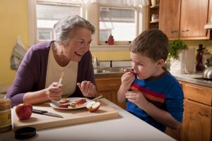 An older woman and a young boy prepare a healthy snack