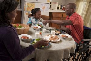 A father, mother and young girl sit at the table for dinner.