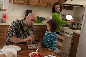 A father and daughter using a food thermometer while mom cooks in the background