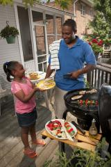 A man taking cooked chicken off of the grill and putting it on a tray held by his daughter