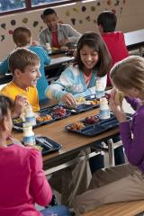 A group of middle school students have lunch in a cafeteria