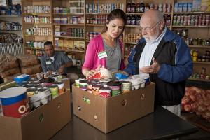 A female food pantry staff member reviews the contents of a box of food with an older adult male recipient.  A male staff member organizes food boxes in the background.