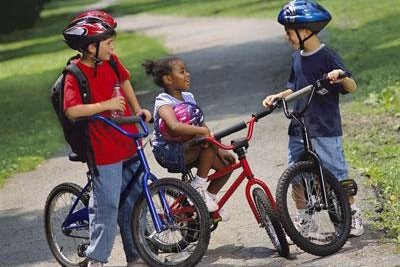 three kids riding bikes outside to school