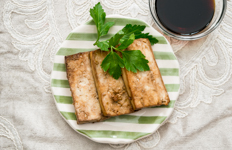 baked tofu on a green and white striped plate with parsley garnish