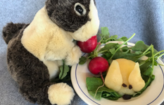 a stuffed bunny eating a radish next to a rabbit shaped out of pears