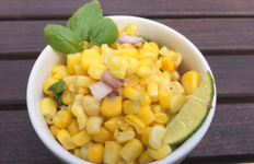 bowl of corn salad garnished with basil and a slice of lime