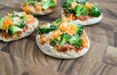 english muffin pizzas with shredded carrots and broccoli