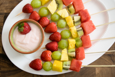 fruit kabobs with watermelon, pineapple, grapes, strawberries, and kiwi on wooden skewers