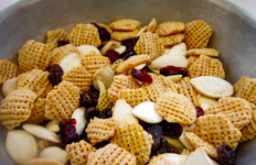 snack mix of cereal squares, pumpkins seeds, almonds, dried cranberries, and raisins in a bowl