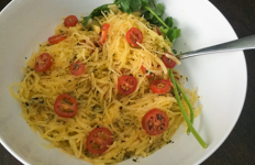 spaghetti squash in a bowl with tomatoes sprinkled on top
