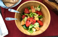 summer salad in a wooden bowl with serving utensils