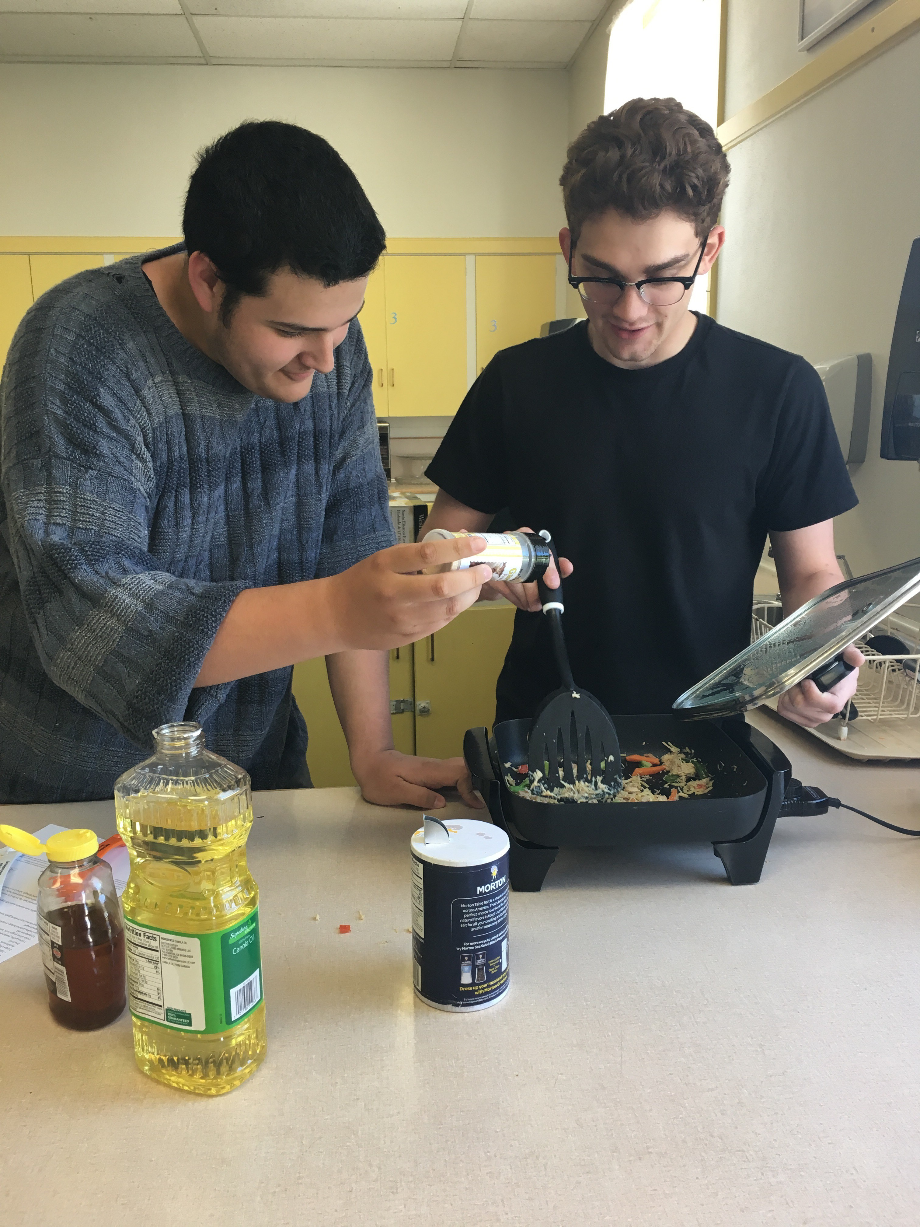two teens cook using an electric skillet