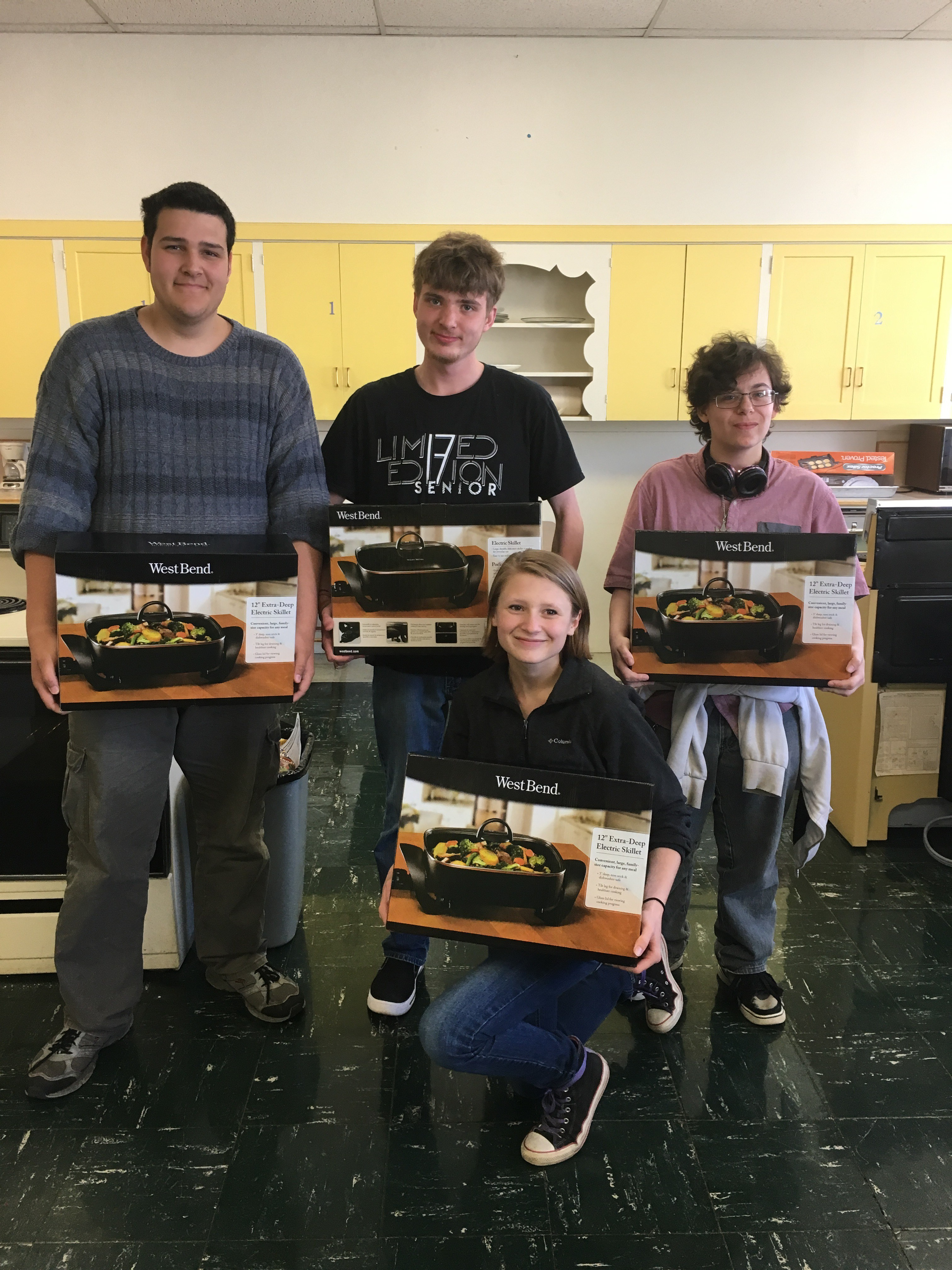 participants pose smiling with their new electric skillets